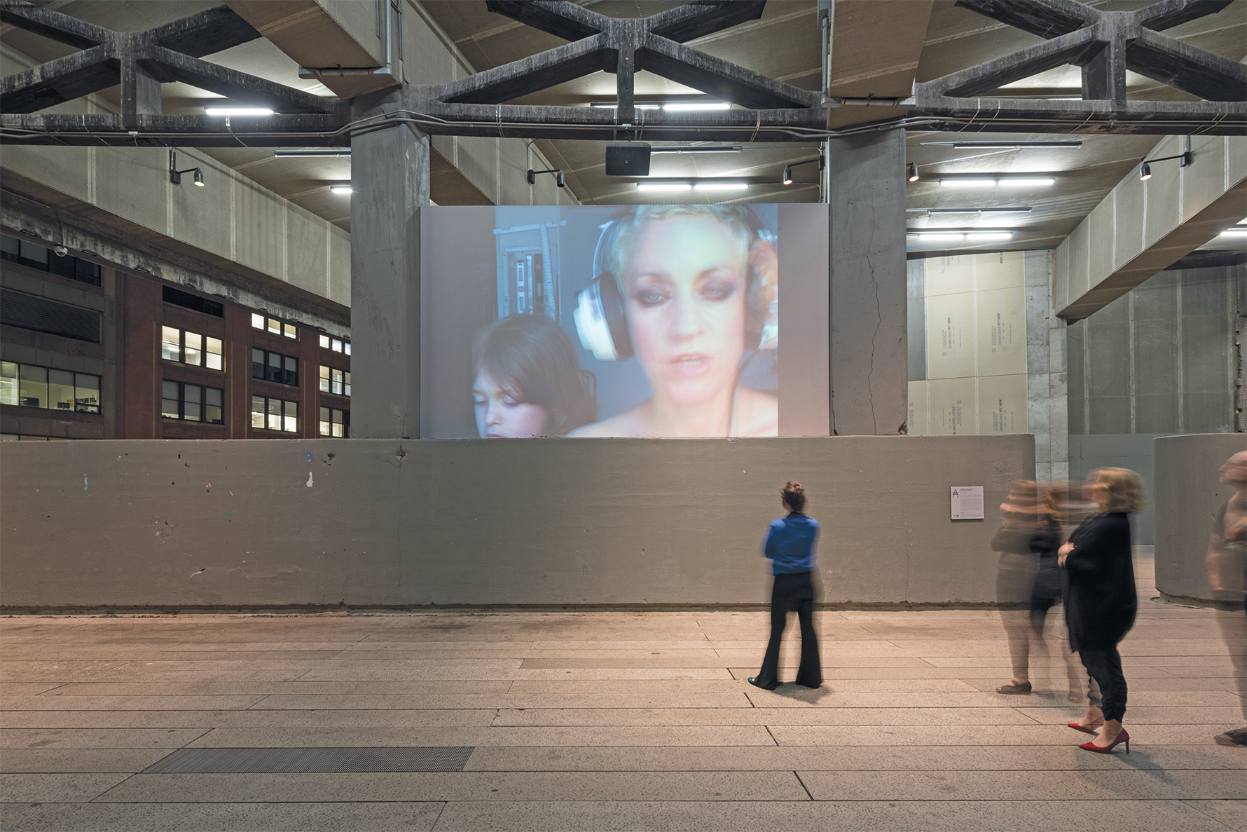 People stopping to watch a video screen that depicts a person wearing headphones