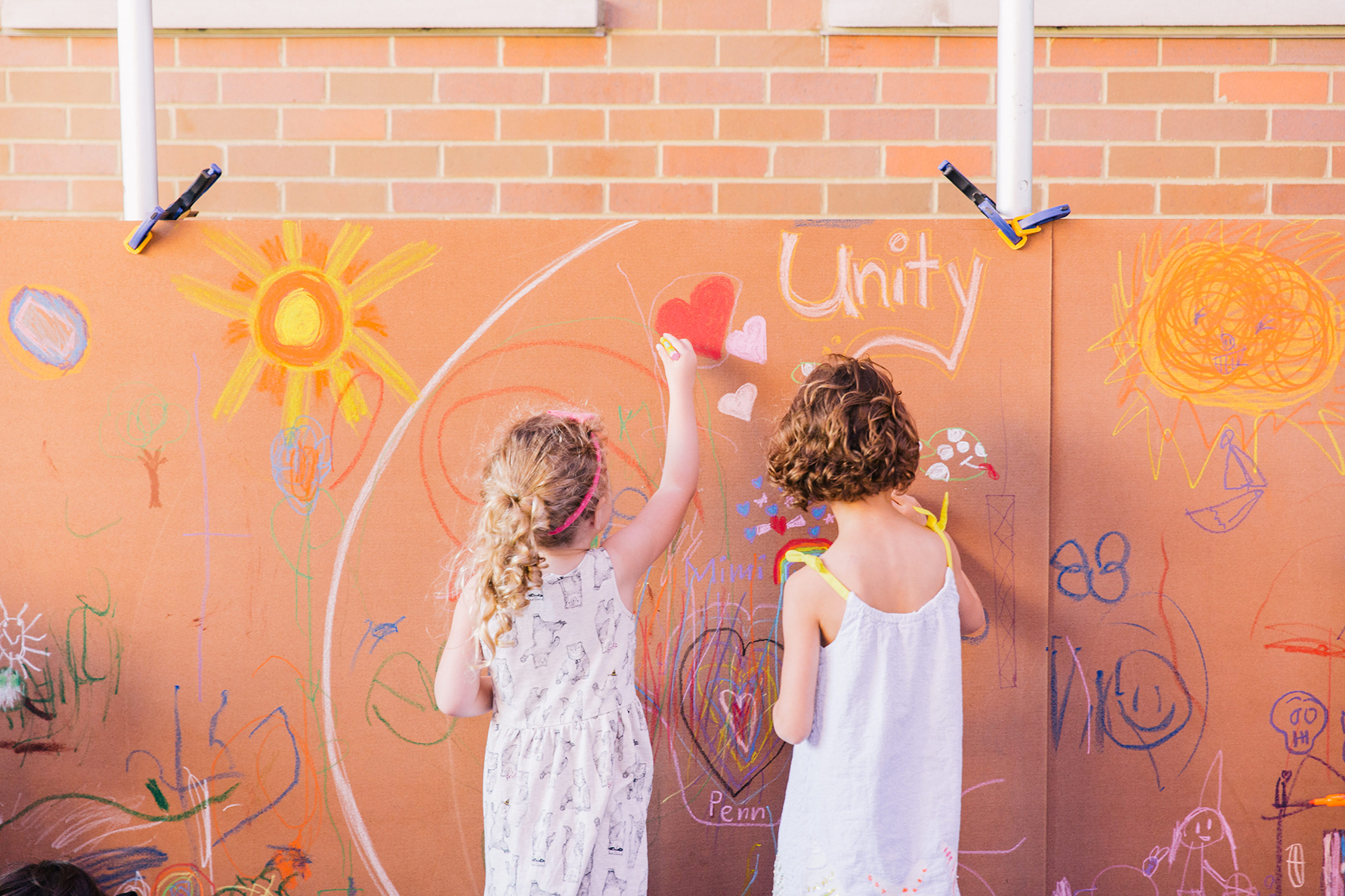 Two children in white summer dresses drawing with chalk on a brick wall