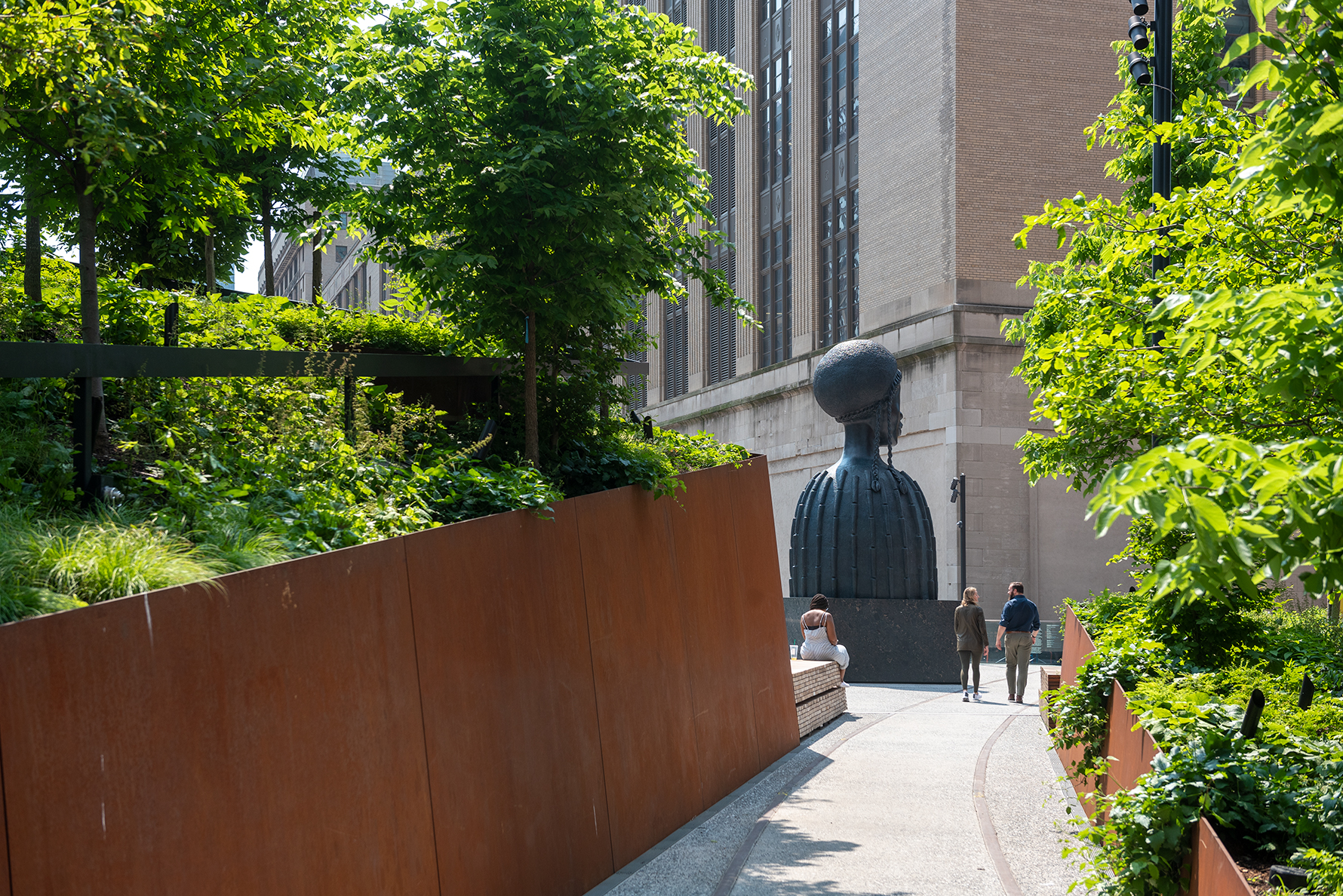 The back of the sculpture Brick House, the 16-foot-tall bust of a Black woman, as seen through a threshold of trees