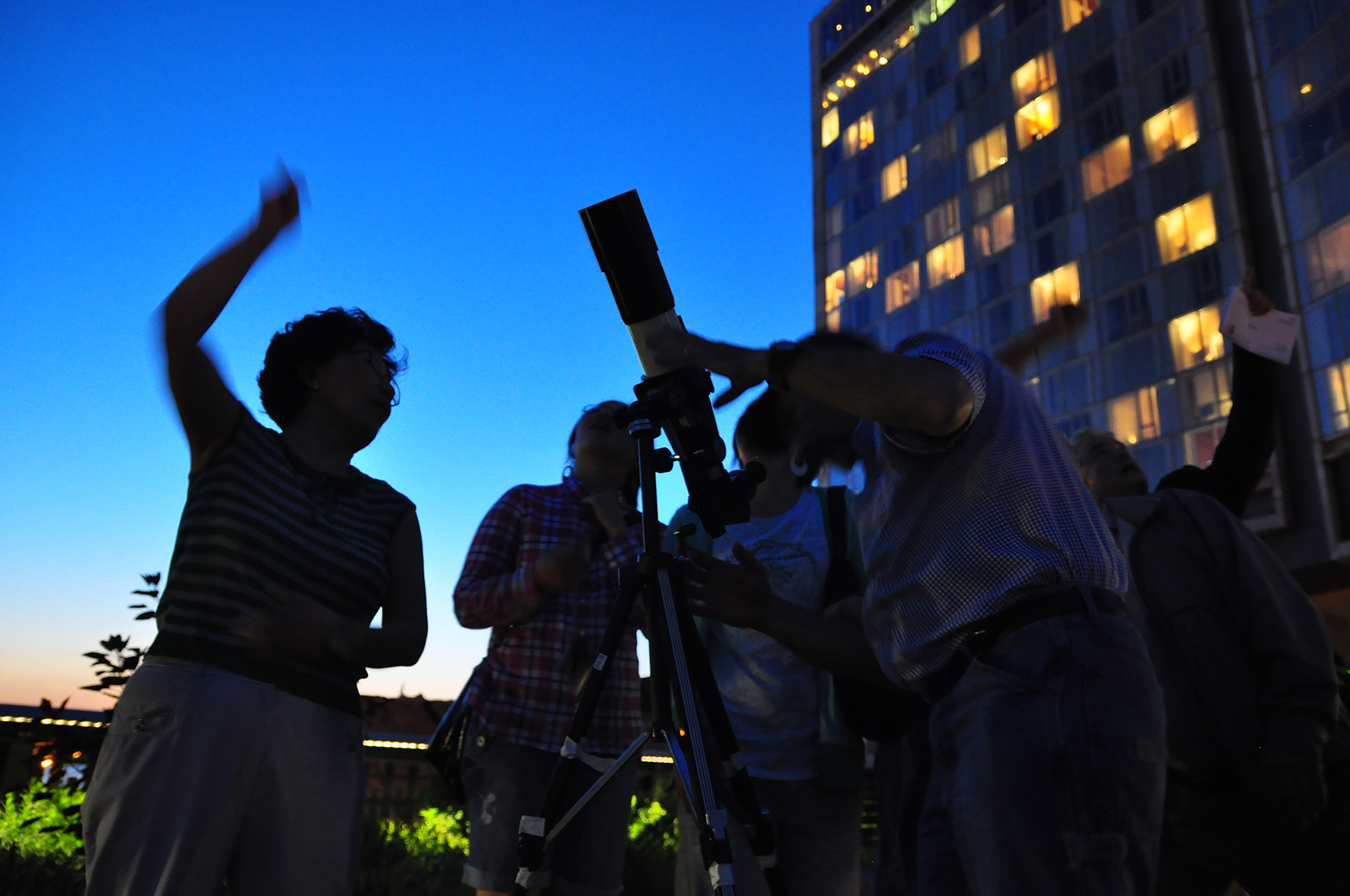 Four people looking at the night sky through a telescope