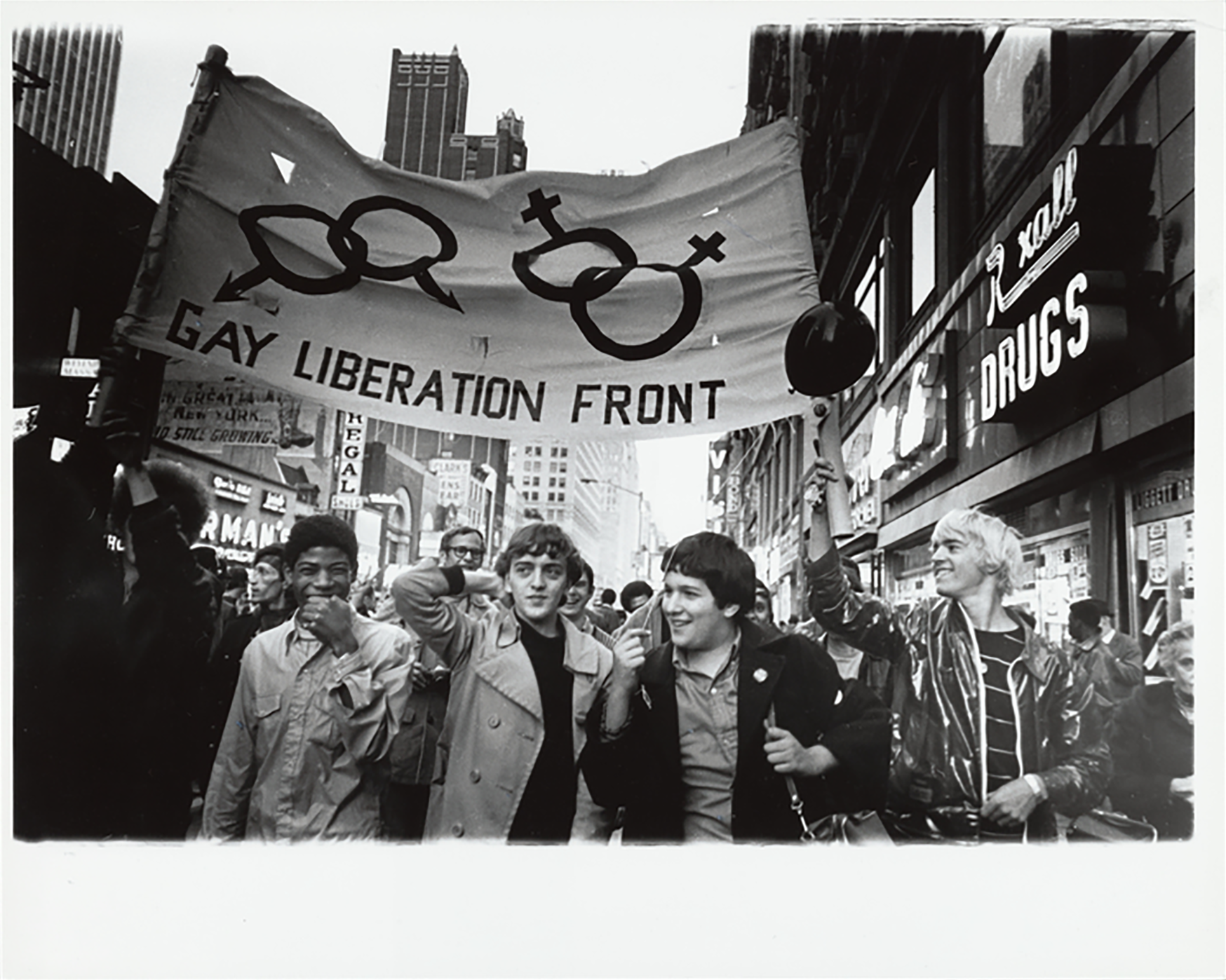 "People marching and holding a sign that reads ""Gay Liberation Front"" with pairs of symbols for men and women"