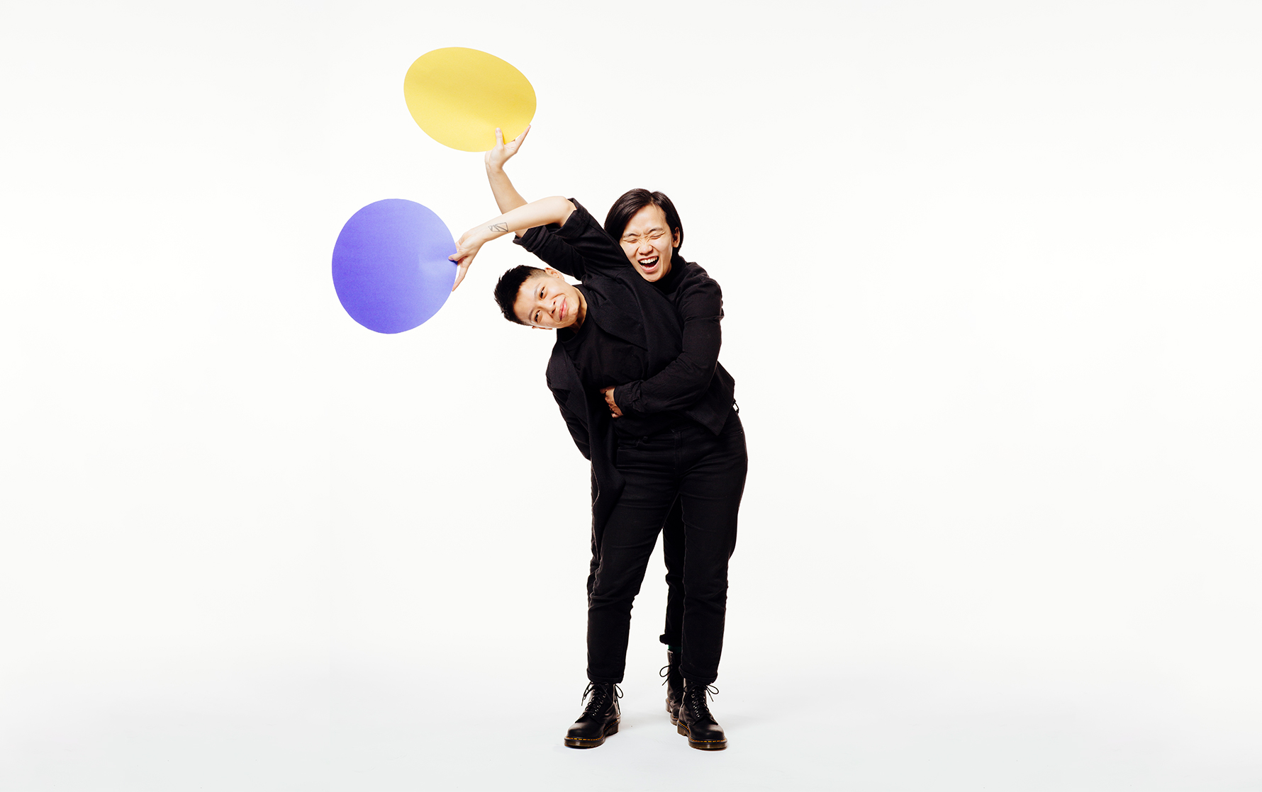 Two people holding a blue dot and a yellow dot.