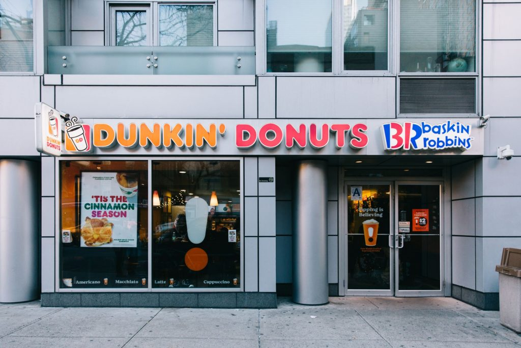 "The facade of a Dunkin' Donuts/Baskin Robbins. The windows display advertising posters including one that says, ""'Tis the cinnamon season"" with photos of a coffee and a croissant breakfast sandwich."