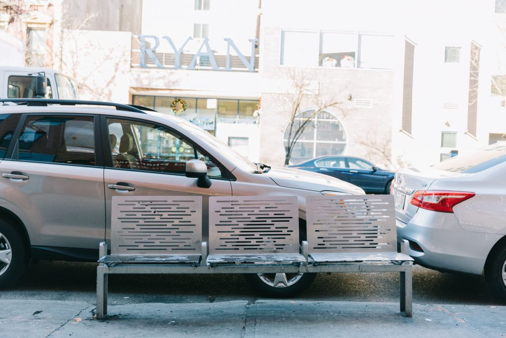 A metal bench with three seats at the edge of the sidewalk in front of parked cars. The bench has short armrests between the seats.