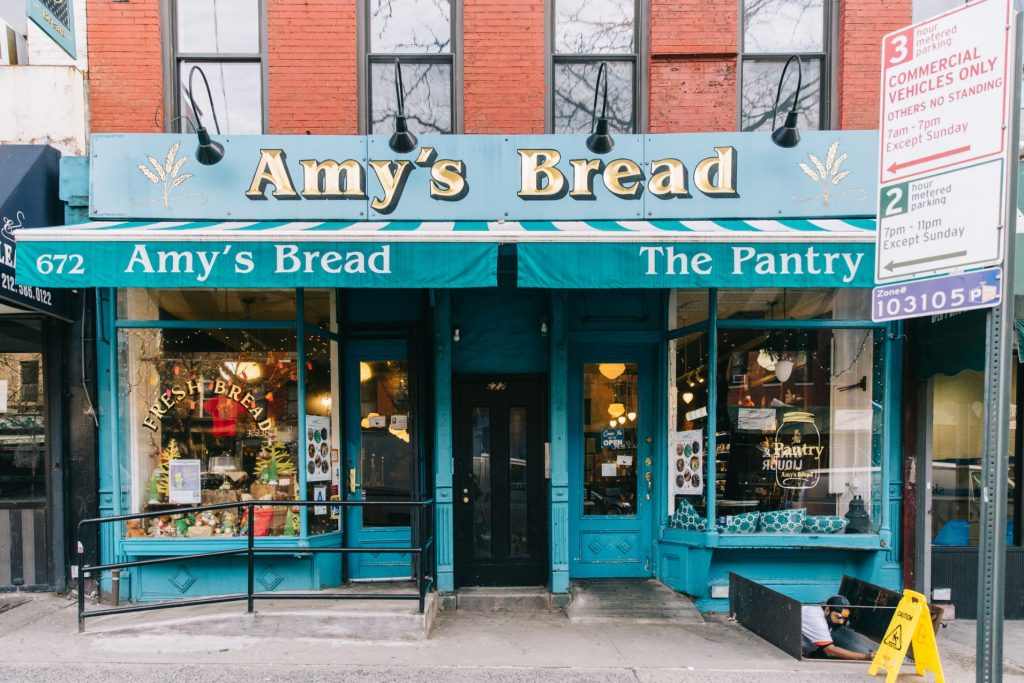 "The facade of Amy's bread. Most of the facade is teal with a few gold accents. Signage reads, ""Amy's Bread"" and ""Fresh bread."" There is a ramp to the entrance."