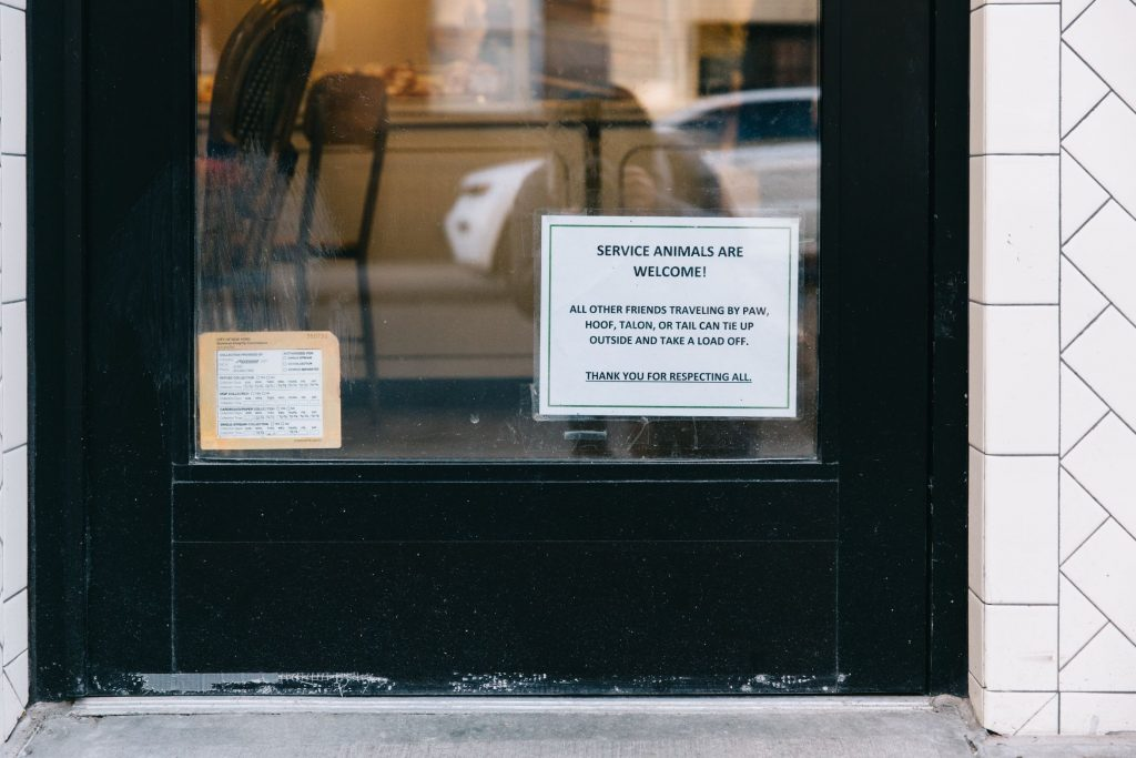 "A close-up of the door of Sullivan Street Bakery showing a sign that reads, ""Service animals are welcome!"""