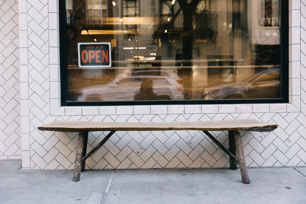A close-up of the facade of Sullivan Street Bakery showing a wooden bench against the white subway tile.