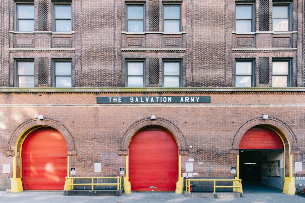 The facade of The Salvation Army. It's brick with lots of brick ornamentation. There are three cargo bays at street level with bright red roll-down doors.