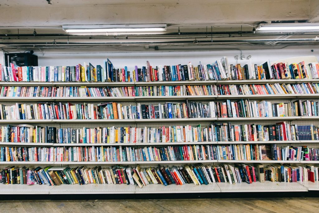 Six shelves of books stretch across the image. The books are multi-colored and some sections have tilted over.
