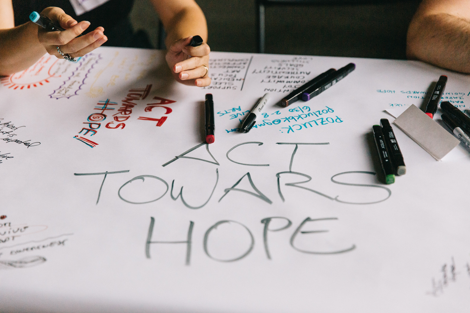 The words ACT TOWARD HOPE on a white piece of paper