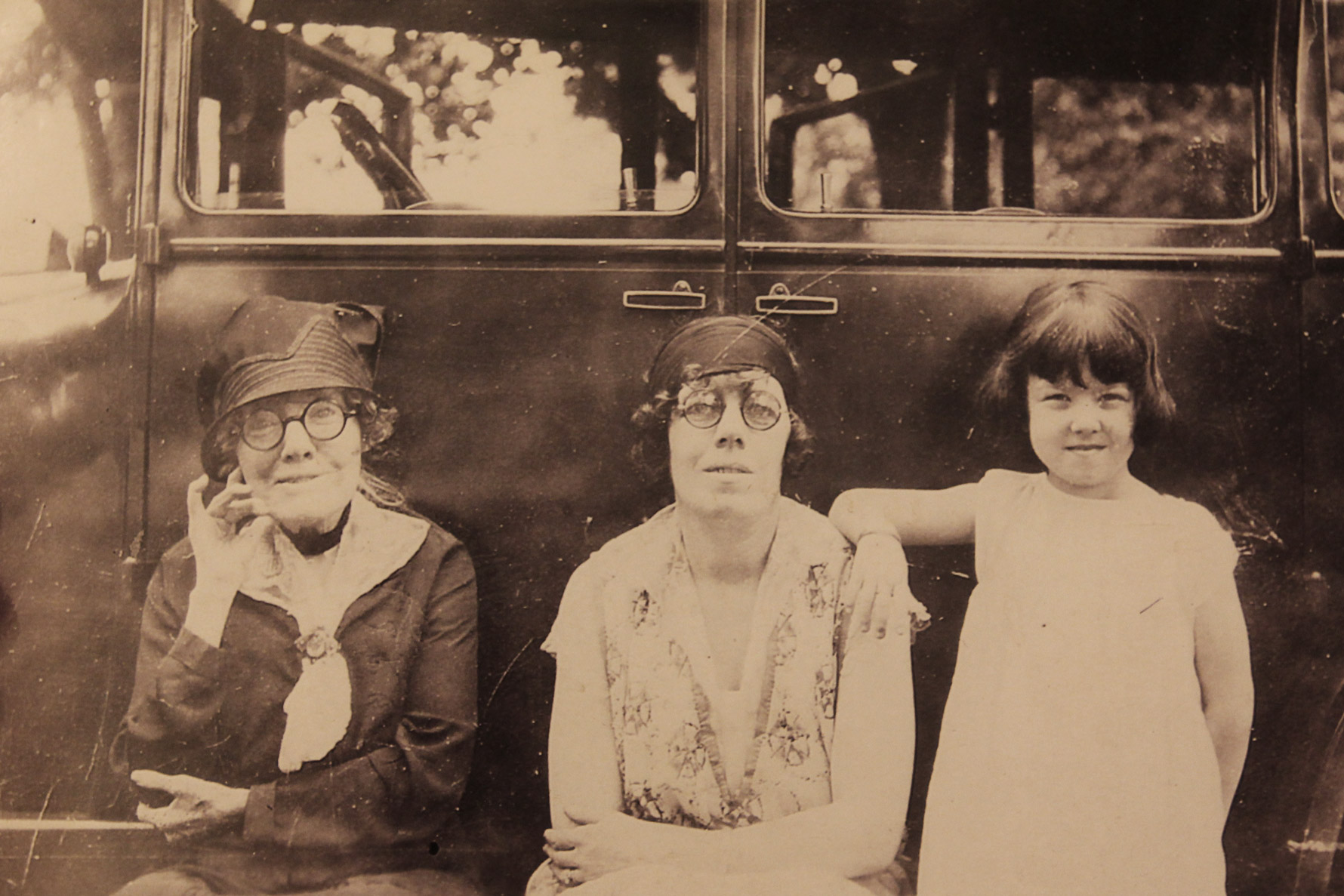 A sepia-toned photograph of three generations of family leaning against a car