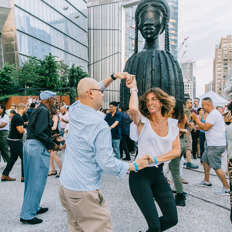 People salsa dancing in front of Simone Leigh's large sculptural bust <i>Brick House </i>>
