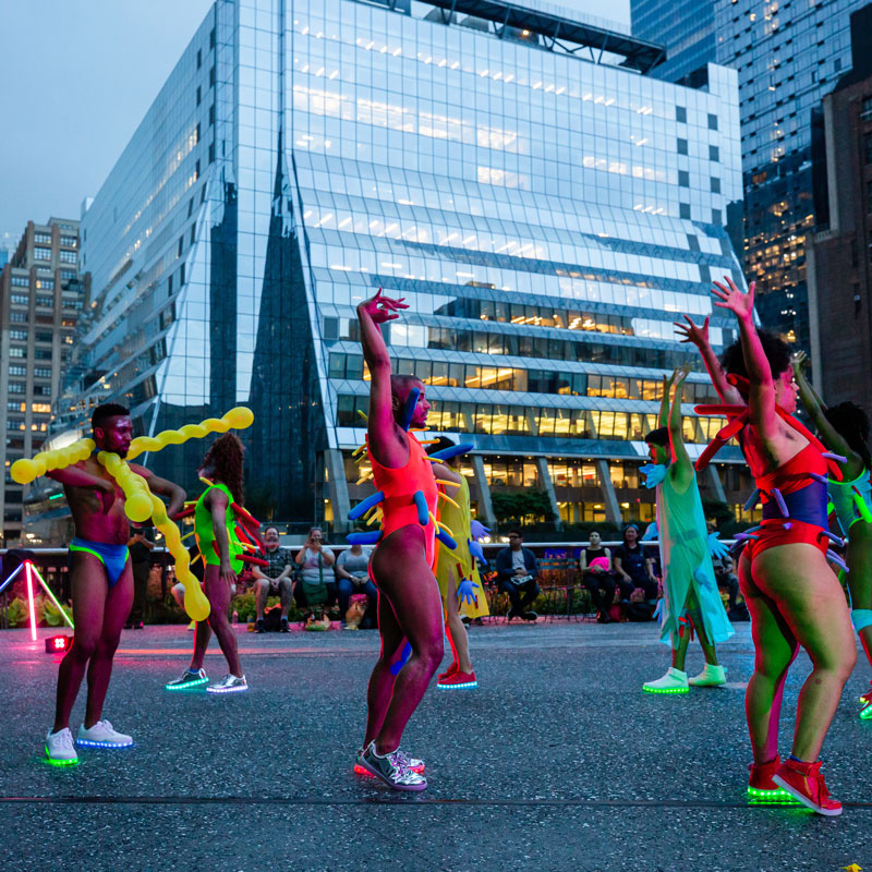 Dancers in neon outfits waving props