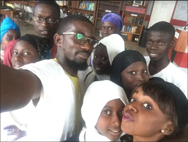 Students and a young entrepreneur share a photo after a workshop training.