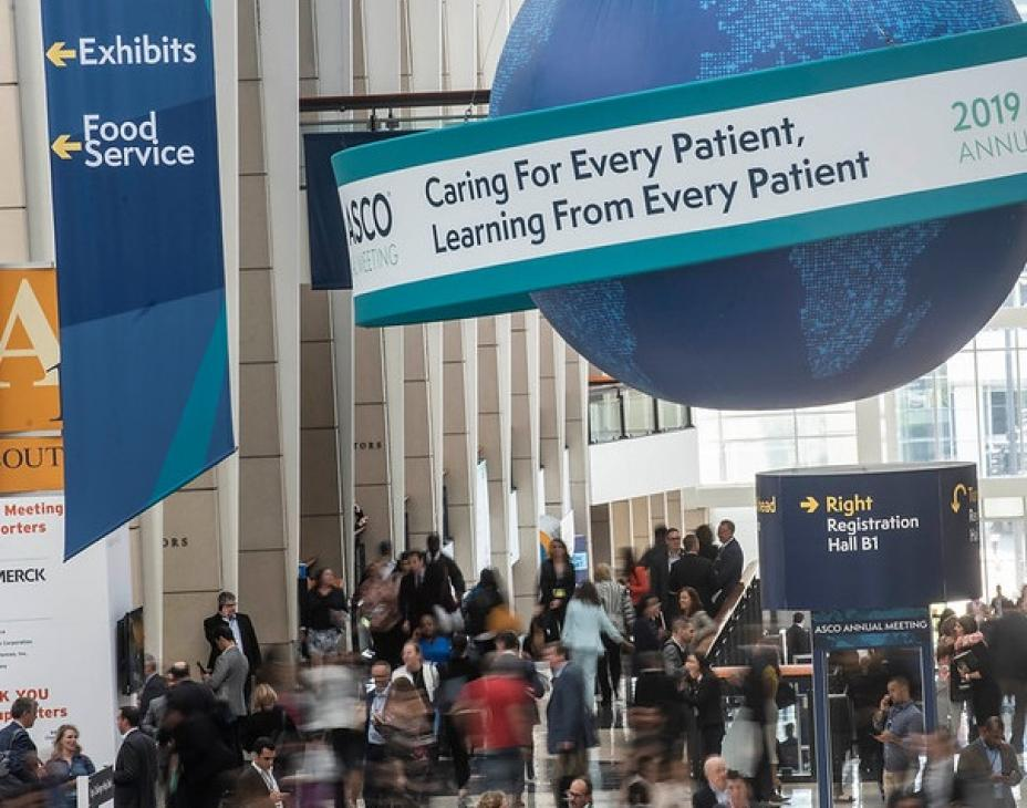 "Elevated view of main hall at ASCO Annual Meeting 2019. People walking in crowd through the large meeting hall space. Large blue globe hanging from ceiling in right-hand side of image. Tagline reads: ""Caring For Every Patient, Learning From Every Patient"""