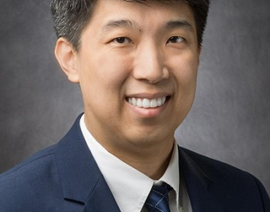 Headshot of Dr. Clinton Yam smiling and looking at the camera, in front of a dark gray backdrop.