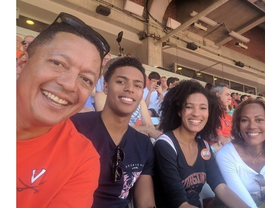 Robinson family sitting together at a stadium taking a group photo. From left to right: father, son, daughter, Monique.
