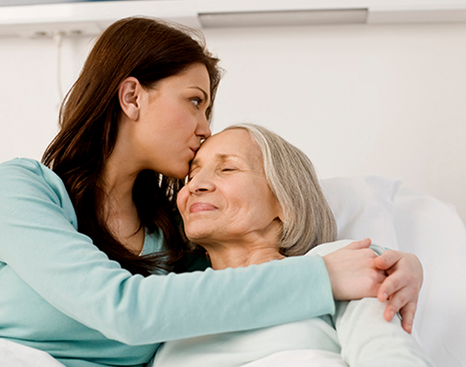 Stock image of adult woman hugging her senior mother