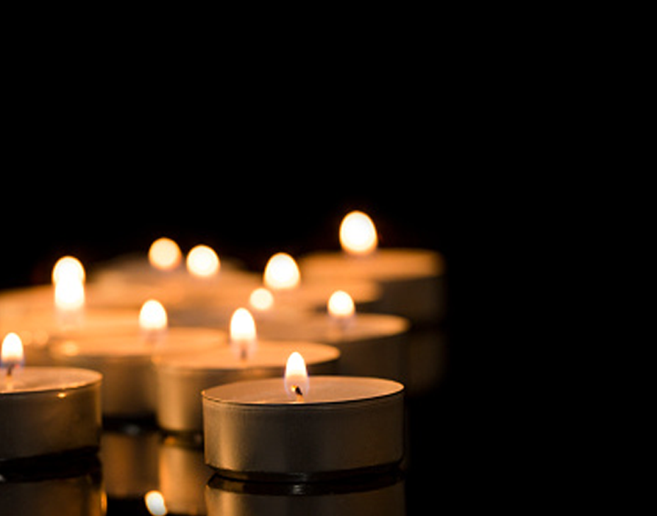 Stock image of lighted tealight candles against a dark background