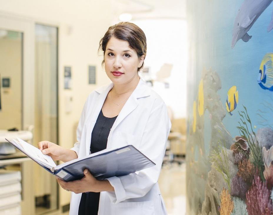 Dr. Elysia Alvarez in a clinical setting, holding an open book, while looking at the camera. The wall to her left is an aquarium painting with marine life. The background features a hospital hallway. She is wearing a white coat.