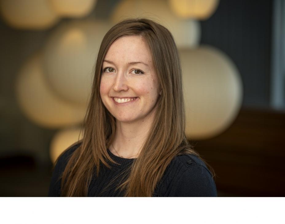 Dr. Molly Taylor smiling facing forward. She has shoulder-length brown hair and is wearing a black shirt.