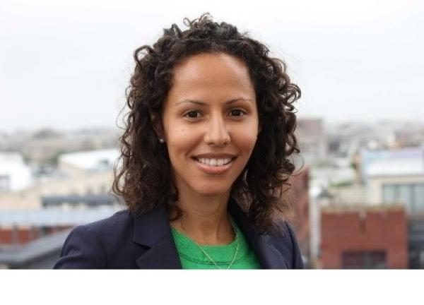Dr. Handy Marshall headshot, smiling at the camera. City skyline in the background, bright gray sky. Wearing a bright green blouse with navy blue blazer. Brown, curly hair.