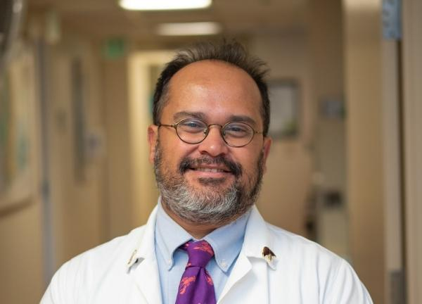 Dr. Flavio Rocha facing forward and smiling. He is wearing a white coat. He's in a well-lit hallway that appears to be in a hospital or clinic.