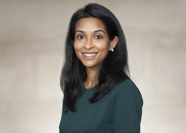 Niloufer Khan, smiling facing forward. She has shoulder-length black hair and is wearing a dark green long-sleeved shirt.