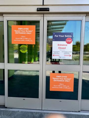 A view of the entrance doors at Mark Craft's hospital, where he goes for cancer treatment. The doors have signs related to COVID-19 warnings.
