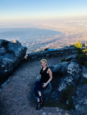 Brenda Brody in athletic gear sitting atop a path overlooking a scenic, atmospheric view of Cape Town, supplemented with a soft, light-blue, cream-yellow horizon in the distance.