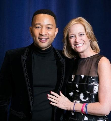 Brenda Brody smiling next to John Legend, the famous singer-songwriter. Both are wearing black clothing and smiling at the camera.