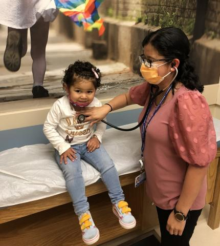 Dr. Jenny Ruiz with a young child patient. The patient appears to be about 3-4 years of age. Dr. Ruiz is wearing a mask and is using a stethoscope on her patient's chest. The patient is gently smiling and facing downward, appearing happy to be in Dr. Ruiz's care.