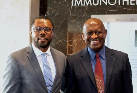 Dr. Kankeu Fonkoua standing with his Resident Travel Award mentor, Dr. Alex Adjei. The two men are smiling, facing forward, and wearing business suits.