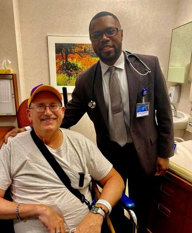 Dr. Kankeu Fonkoua standing next to his patient, who is sitting down. Both men are smiling, facing forward; both men appear to be in a clinical setting.
