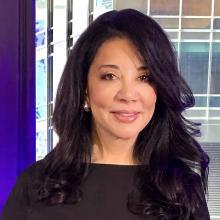 Deanna B. van Gestel wearing a black dress, with shoulder-length dark brown hair, smiling gently and facing forward.