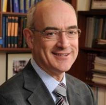 Headshot of Dr. Everett Vokes wearing a dark gray suit, a pair of glasses, and smiling at the camera
