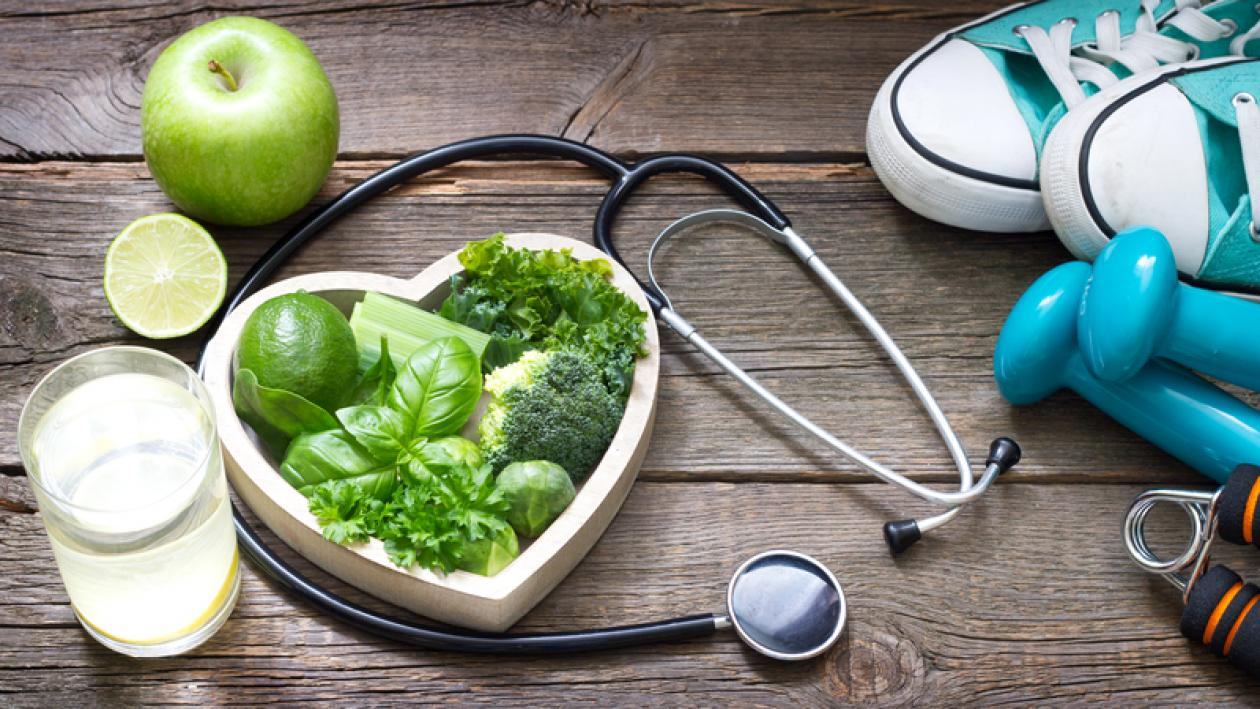 An image with a heart-shaped bowl with green vegetables, a doctor's stethoscope, pair of running shoes, hand weights, a glass of water, and a green apple