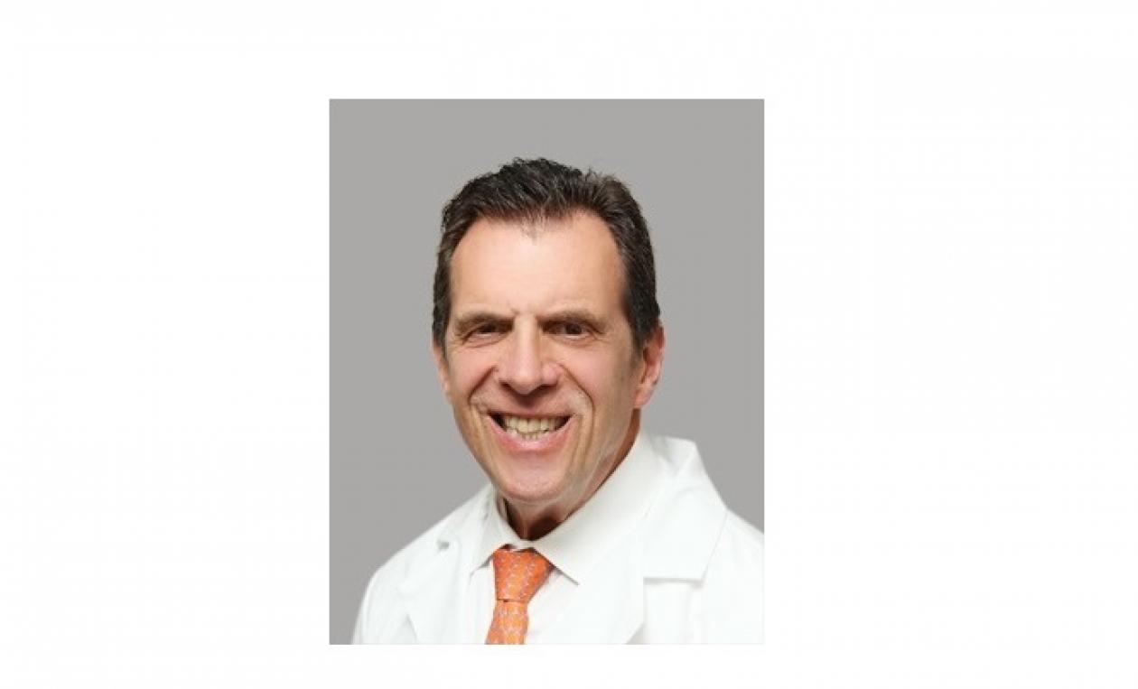Dr. Marc Citron smiling, facing forward. He is wearing a white coat with a bright orange tie.
