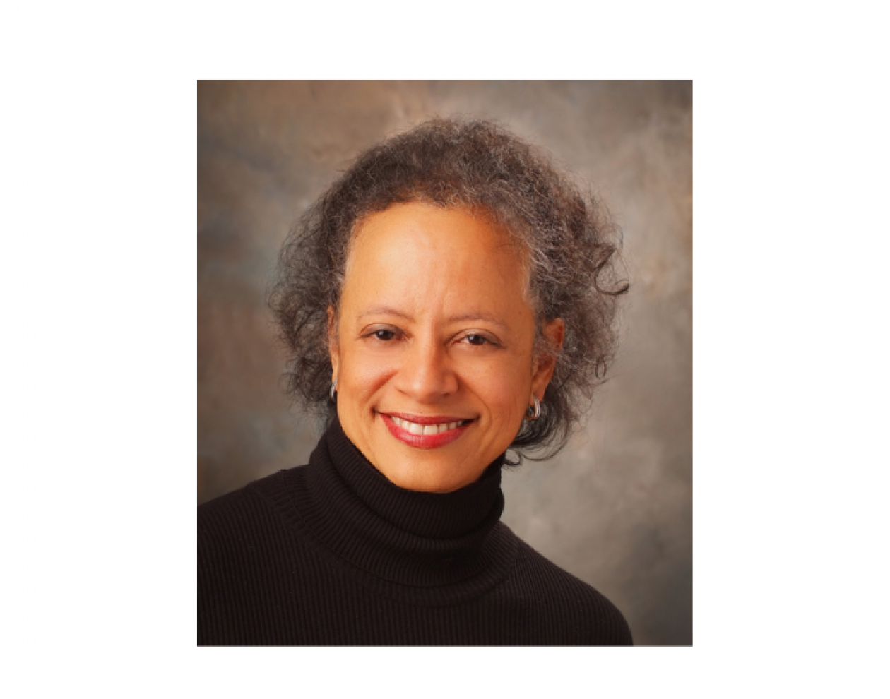 Dr. Lori Pierce wearing a black neck-collar sweater. She is smiling facing forward.