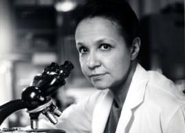 Dr. Jane C. Wright in a lab coat using a microscope to conduct clinical research