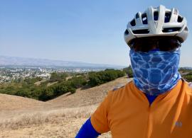 Mark Crafts in an orange shirt, silver helmet, black sunglasses, and electric-blue face-mask