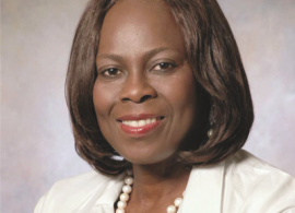 Dr. Olopade headshot. She is smiling, facing forward, wearing a white jacket, with a white pearl necklace.