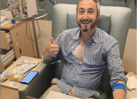 Dave Thau in a clinical setting, smiling and holding a thumbs-up. He has a monitor attached to his chest and is sitting, with a laptop.