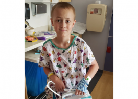 Cain, a 12-year-old patient with Ewing sarcoma, wearing a hospital gown and facing forward