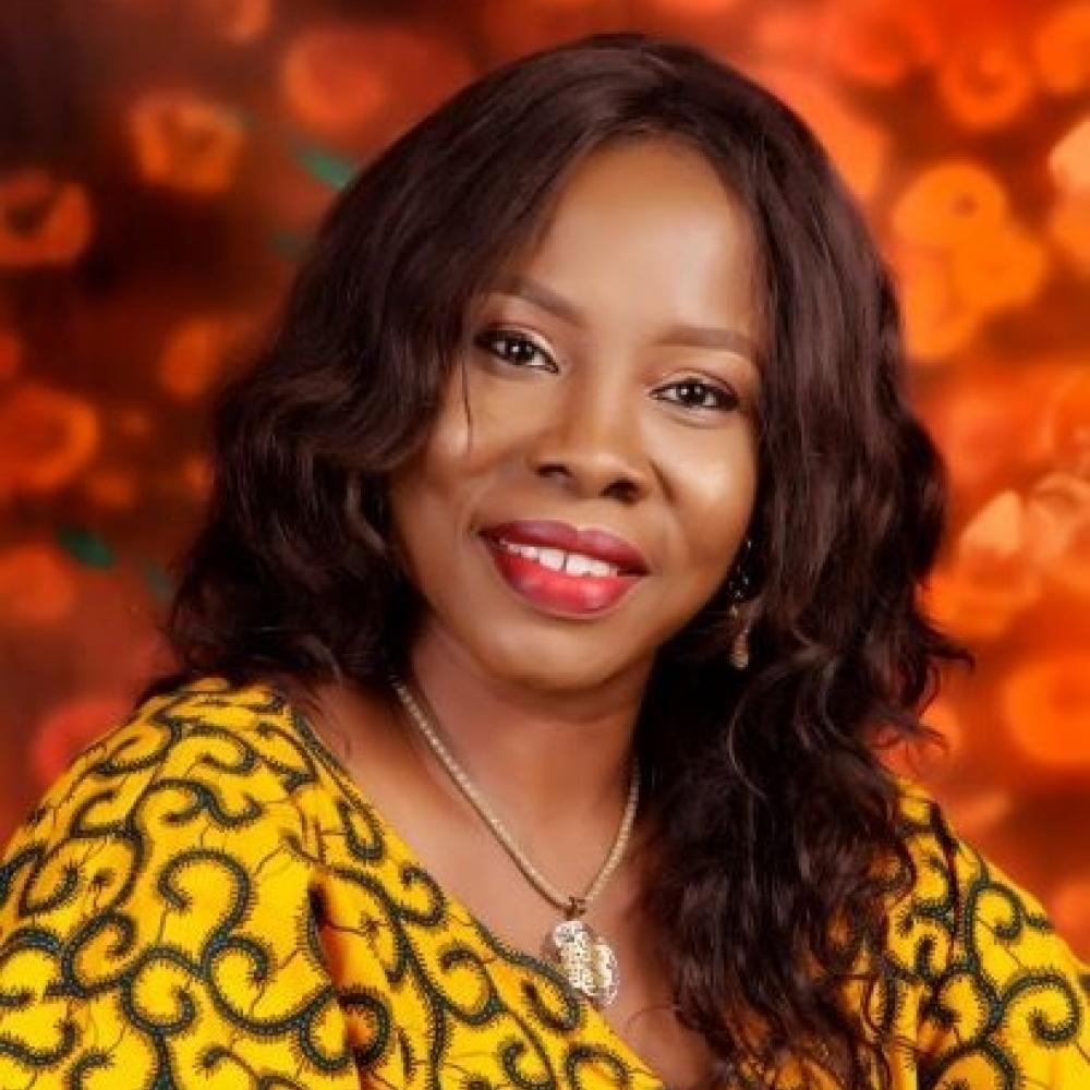 Headshot of Dr. Tonia Onyeka smiling. Background is bright, deep orange. Dr. Onyeka is wearing a gold-colored long-sleeve shirt with an intricate pattern colored dark brown to black.