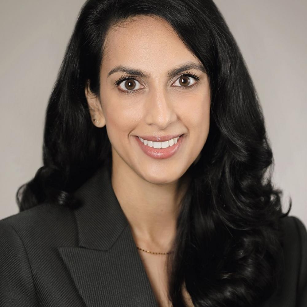 Dr. Lekha Mikkilineni smiling facing forward; headshot from chest up. She is wearing a black blazer and has long black hair.