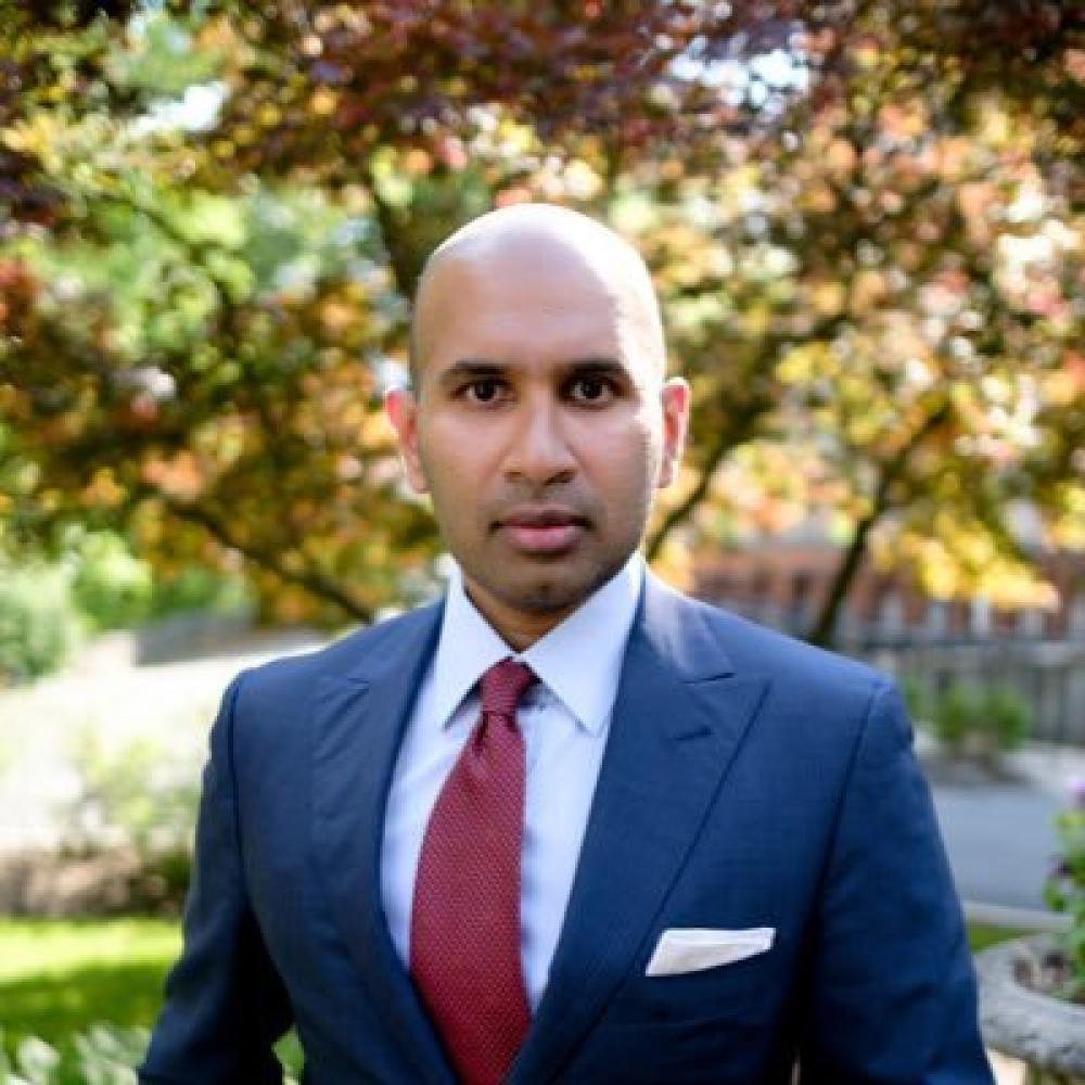 Dr. Davar in a blue suit facing forward with a rather serious demeanor. He is outdoors with autumn trees in the background.
