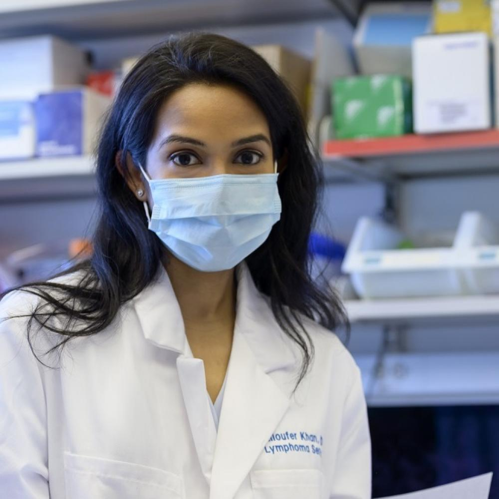 Niloufer Khan, wearing a medical white coat and a mask, facing forward. She is in a clinical laboratory settings, holding a document.