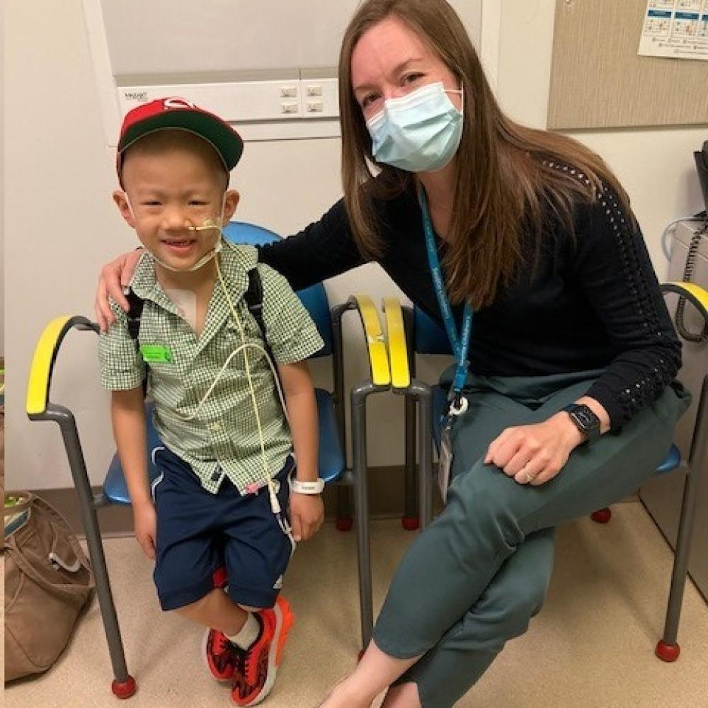 Dr. Molly Taylor sitting with a patient. Dr. Taylor is wearing a mask, black shirt, and jeans. Her patient appears to be very young, is wearing a green shirt, blue shorts, and a red cap. Both are smiling and facing forward.