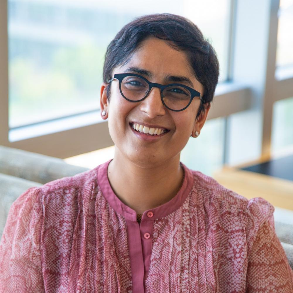 Dr. Salvia Jain smiling facing forward. She's sitting in a bright room with natural light. She's wearing a light pinkish-red shirt and reading glasses, and has short black hair.